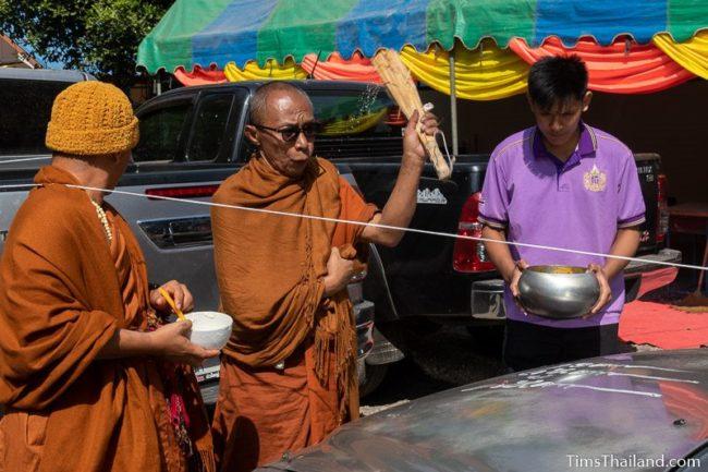 monk splashing water on a car