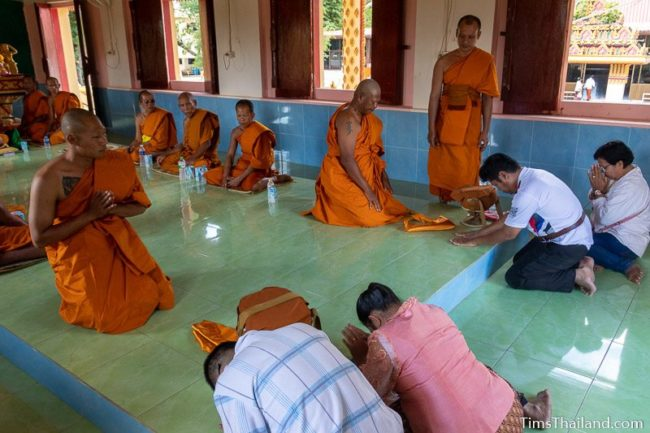 parents bowing down before men about to become monks