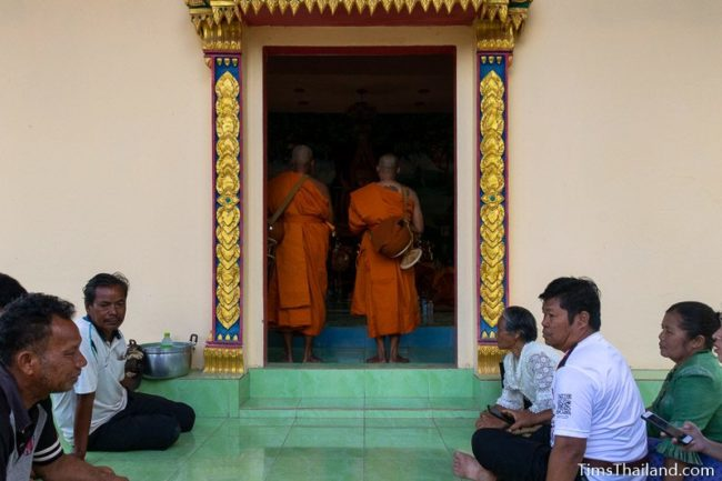 men about to become monks standing in doorway of ubusot