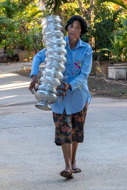 woman carrying a tall stack of rice bowls