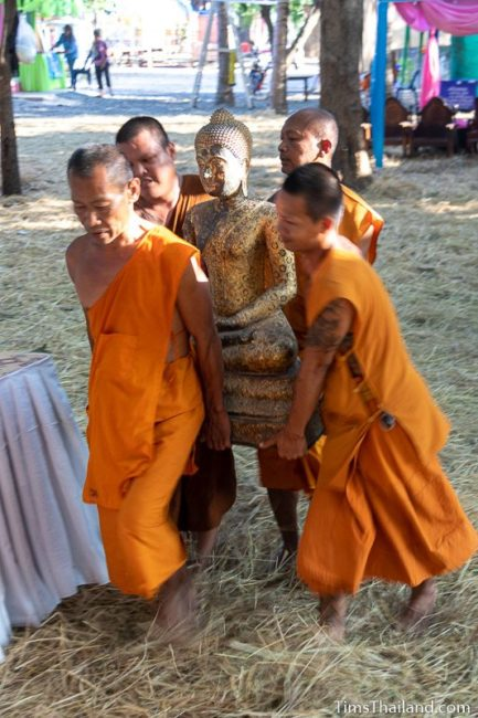 monks carrying a Buddha statue