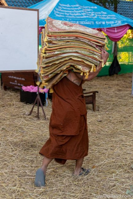 monk carrying a pile of meditation mats