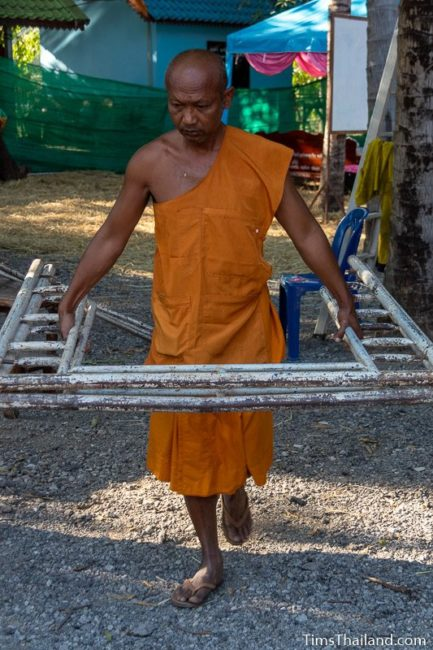 monk carrying a piece of scaffolding