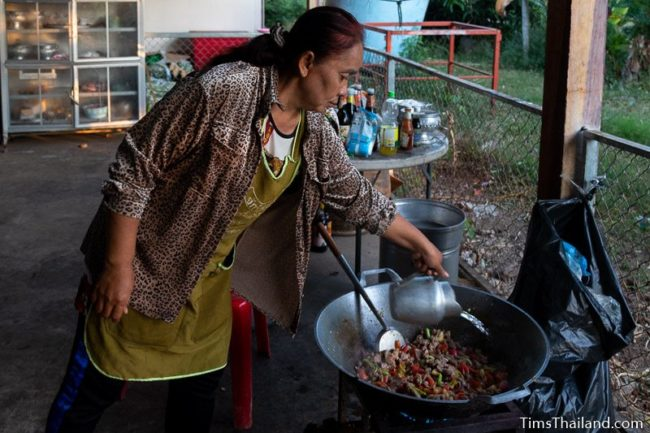 woman pouring water into a giant wok