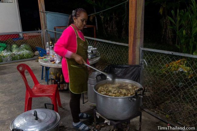 woman stirring food in a giant pan