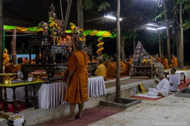 monk lighting candles in front of a Buddha image