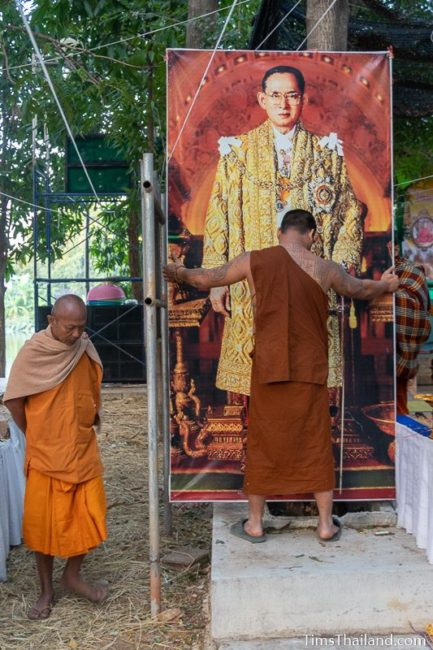 monks putting up a picture of King Rama 9
