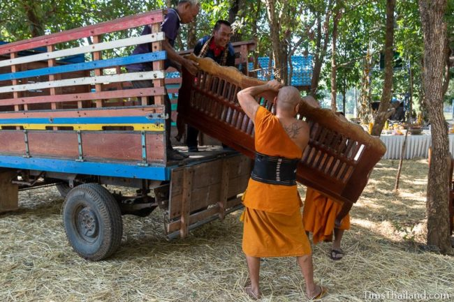 monks loading a bench onto a truck