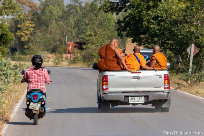 monks riding in back of pickup truck