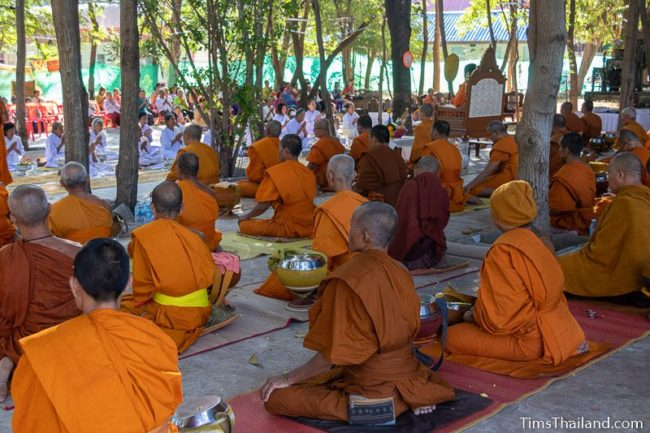 monks and people in white listening to a sermon