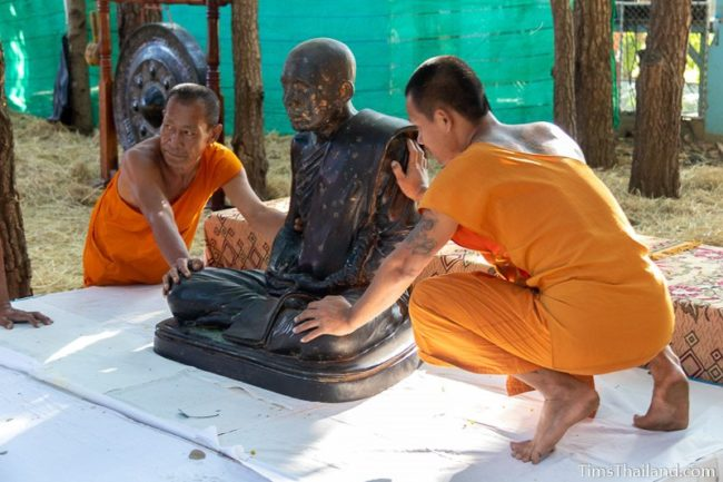monks moving a monk statue