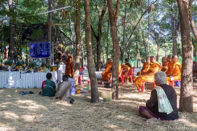 monk leading ceremony in front of monk statue