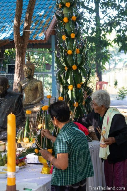 people lighting incense around a monk statue