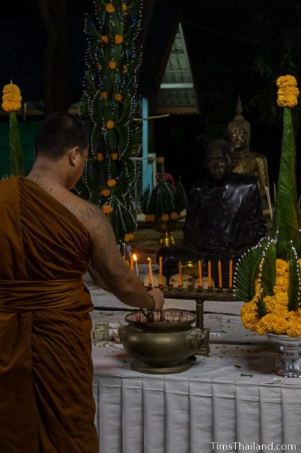 people lighting incense in front of a monk statue