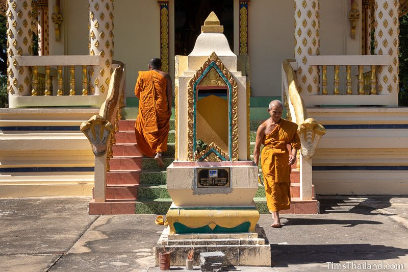 two monks walking in and out of ubosot
