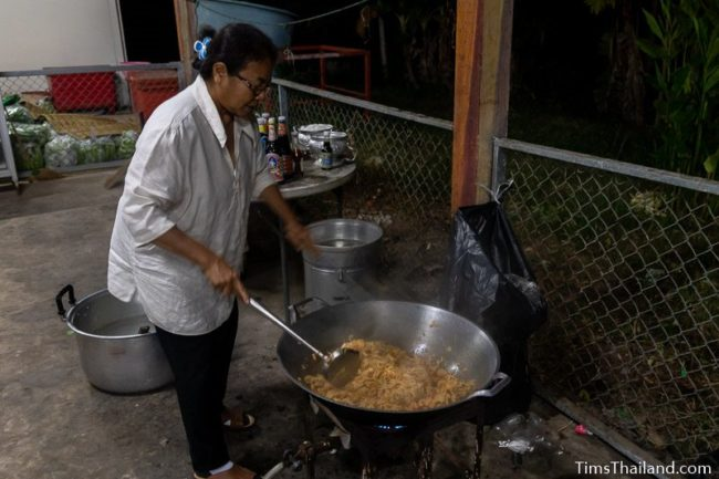 woman cooking in giant wok