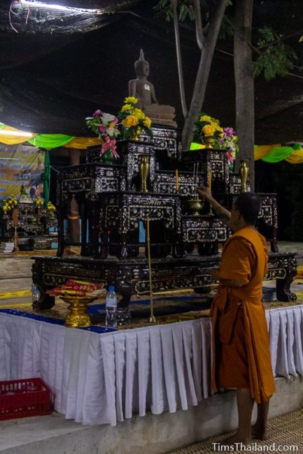 monk lighting incense in front of Buddha image