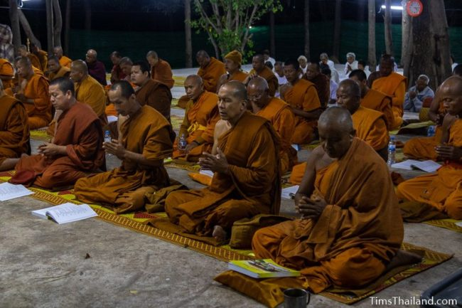 monks and people in white chanting during the night
