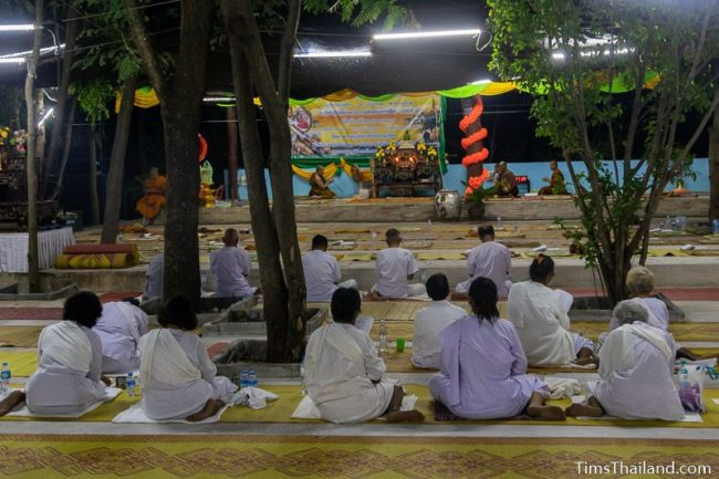 people in white meditating during the night