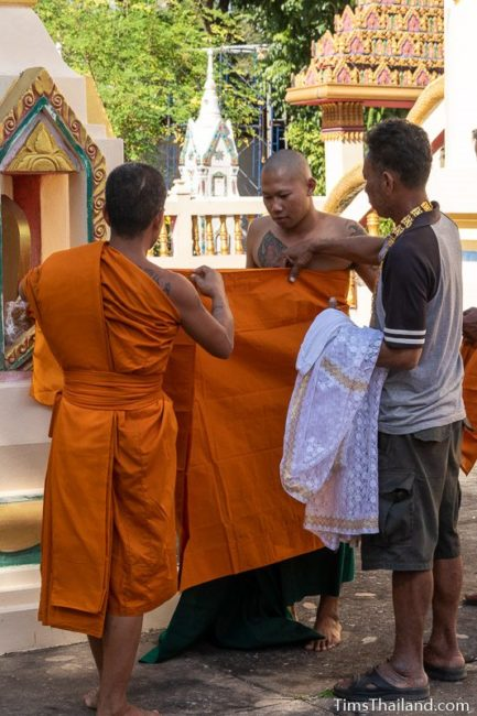 monk helping a man ordaining to be a monk put on his robes