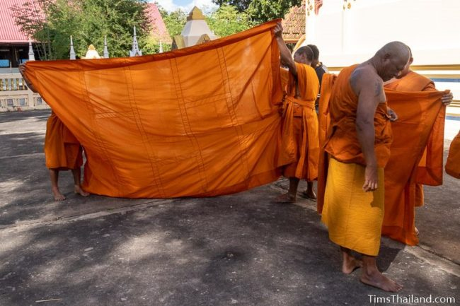 monks helping men ordaining to be monks put on their robes