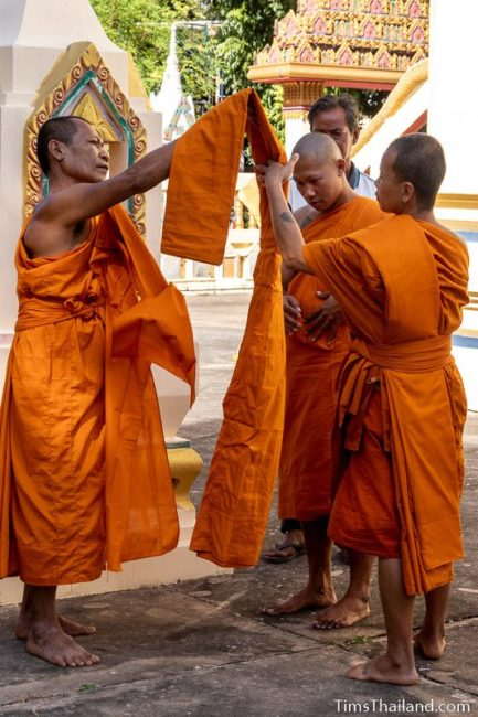 monks helping a man ordaining to be a monk put on his robes