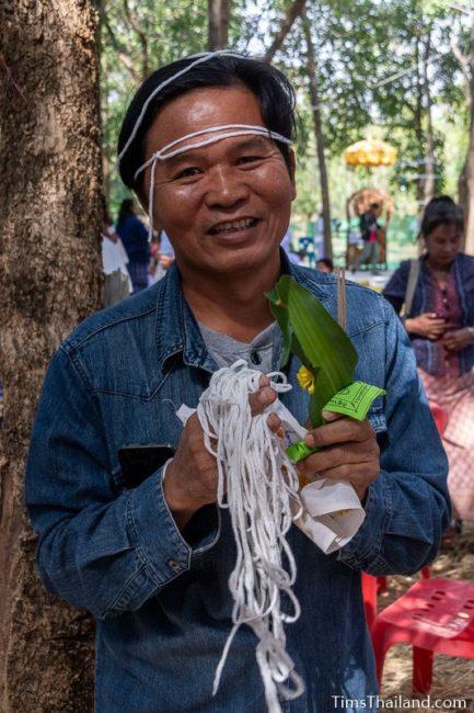 man holding white string