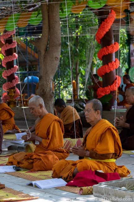 monks sitting with white strings tied above them