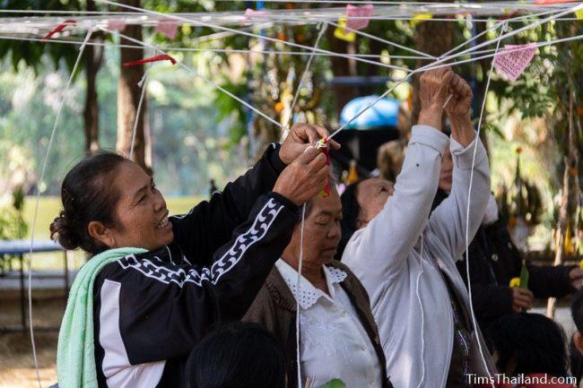 people tying white strings