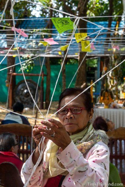 woman tying white strings