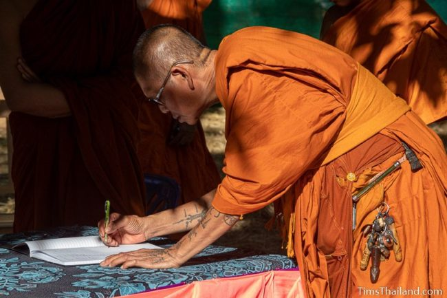 monk signing his name in a notebook