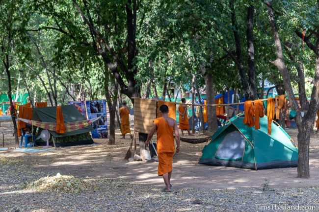 monks walking amidst tents
