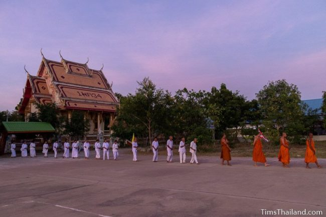 monks and people in white doing walking meditation