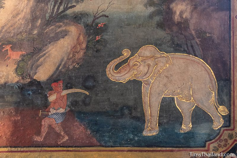 mural painting of a gold-trimmed elephant and a man taking one of his tusks
