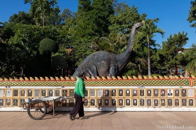 man walking past dinosaur statue