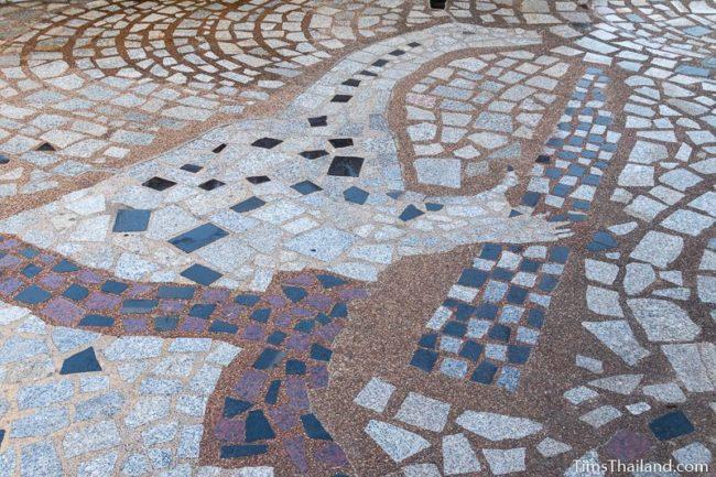 floor mosaic of dinosaur playing a kaen