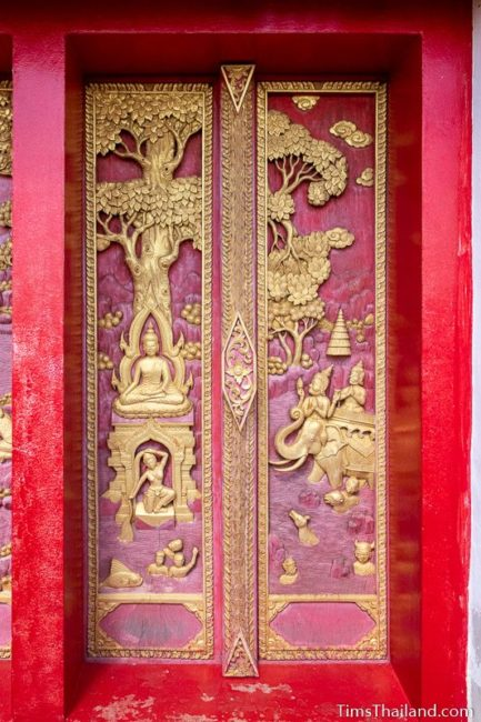 carved wood doors with Buddha battling Mara