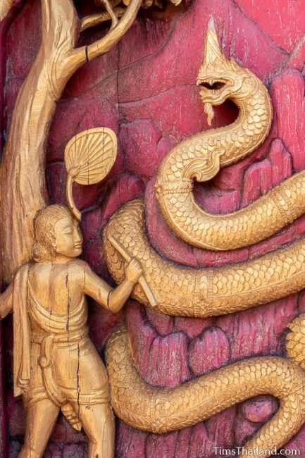 woodcarving of a man and a naga