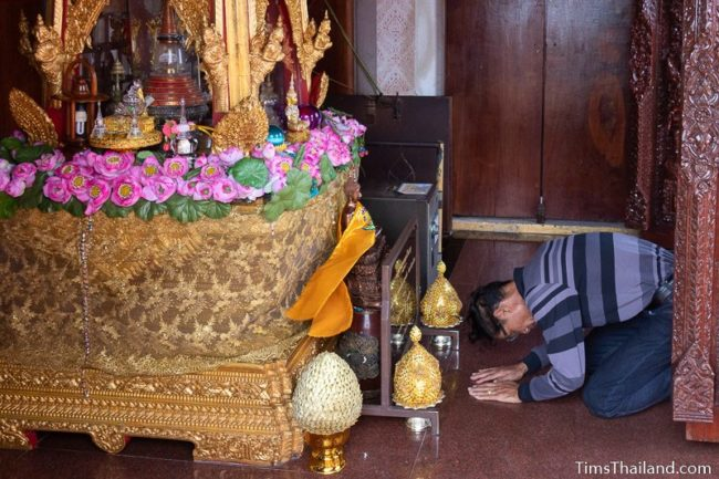 man praying in front of Buddha relic chamber