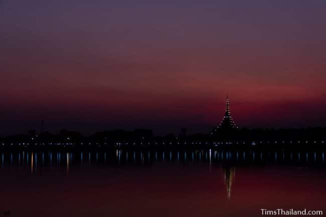 stupa seen from across a lake at sunset