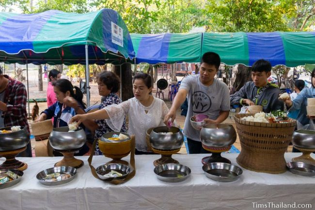 people putting food in monk bowls