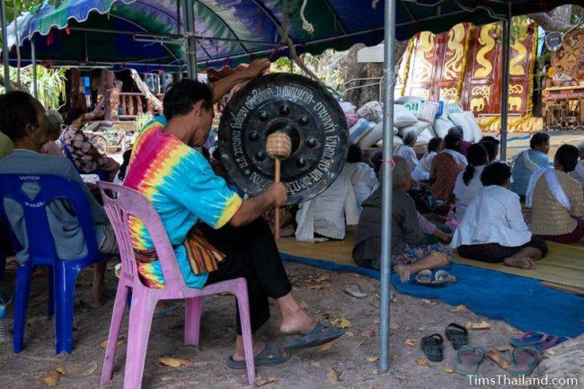 man banging a gong
