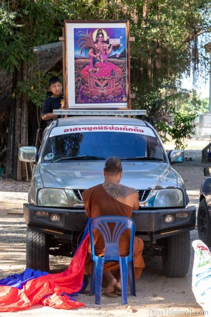 monk tying folded fabric to front of pickup truck