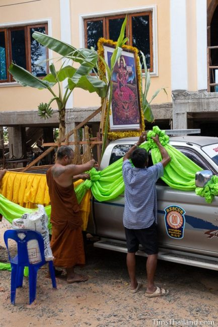 monk and man tying folded fabric on pickup truck