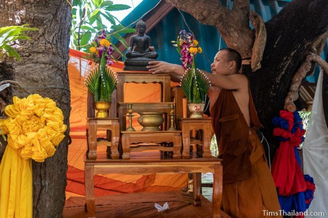 monk placing Buddha image on a table