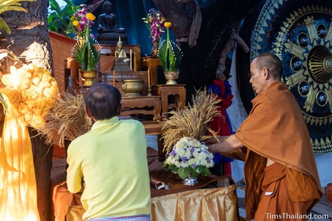 man and monk putting rice in front of a Buddha image