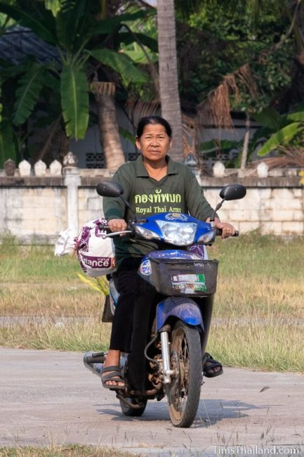 woman bringing rice to the temple on back of a motorcycle