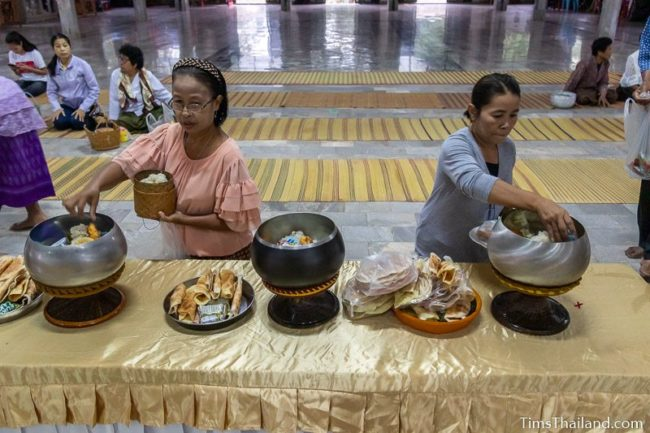 women putting food in monk alms bowls