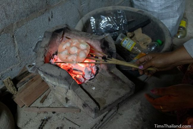 closeup of grilling khao griap in the dark of night