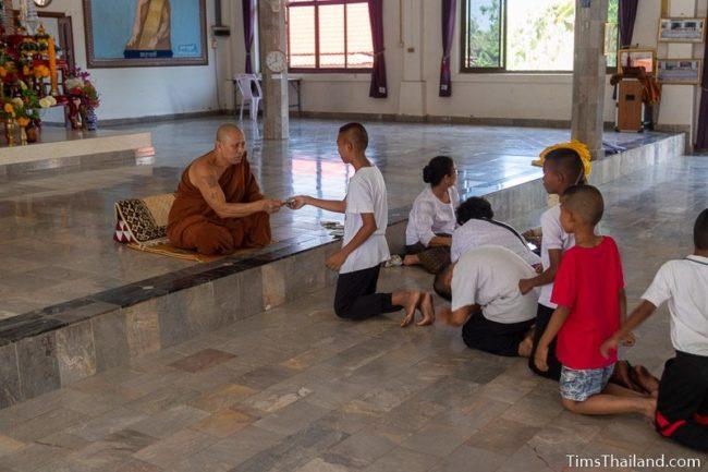 children in line to get money from monk